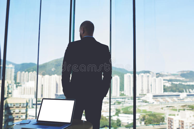 Metering room office table and open net-book with mock up copy space screen for your advertising. Back view of man professional lawyer in suit is looking into stock photo