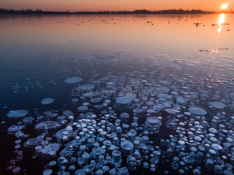 Methane bubbles in ice. Methane bubbles in the ice a of a freshly frozen Paezeriai lake in Lithuania during sunset stock image