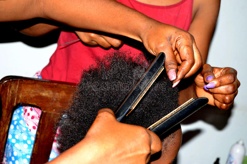 METHOD OF FLEXIBILITY. An African hairdresser using a modern babyliss straightener to soften natural frizzy hair in order to style it easily royalty free stock photography