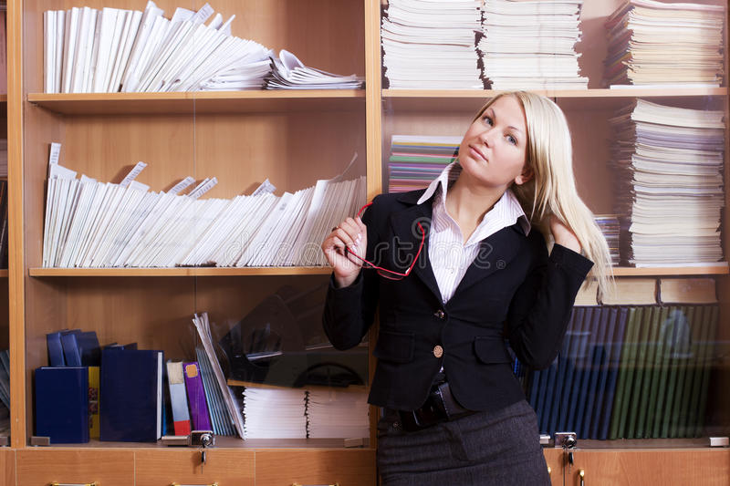 Methodical office. Young attractive blonde in business clothes on at the workbook room stock photo
