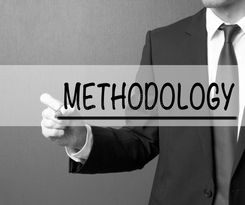 Methodology. Businessman in a suit with a marker writing on visual screen.  stock photography