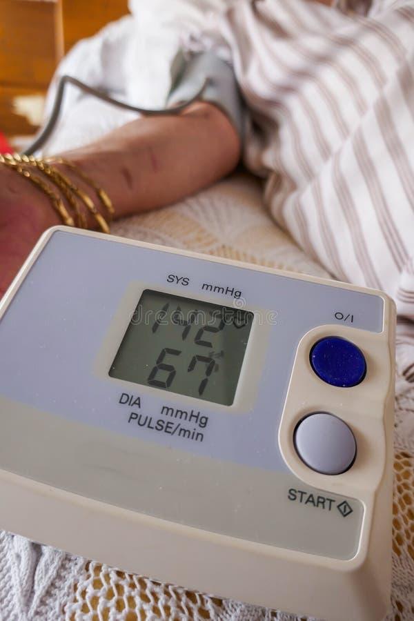 Meting van druk, een vrouw die haar bloeddruk en impuls controleren op haar wapen royalty-vrije stock foto's