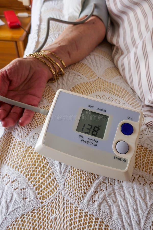 Meting van druk, een vrouw die haar bloeddruk en impuls controleren op haar wapen stock foto's