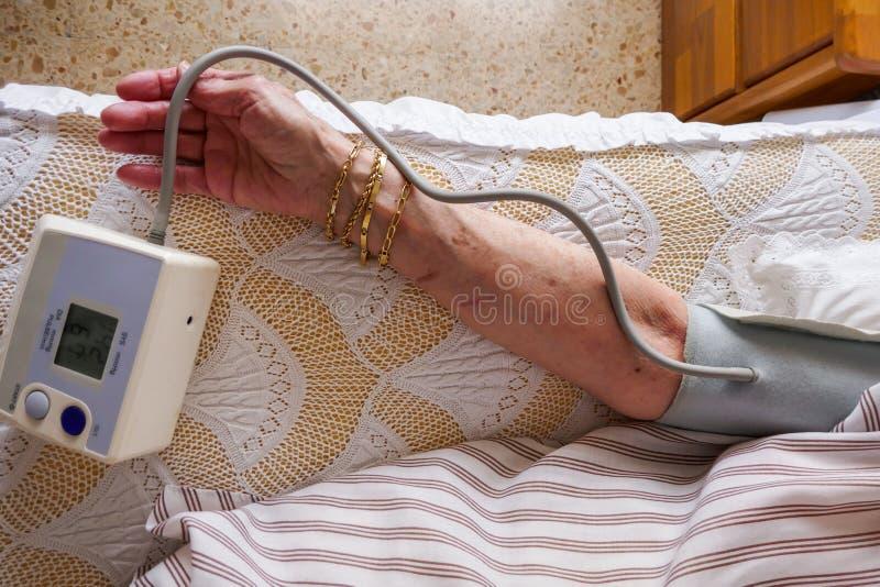 Meting van druk, een vrouw die haar bloeddruk en impuls controleren op haar wapen royalty-vrije stock foto