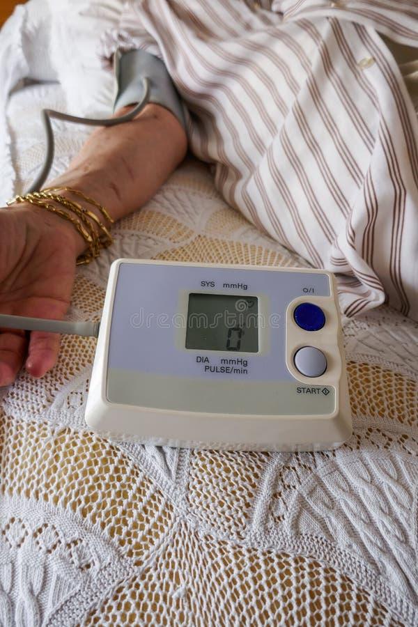 Meting van druk, een vrouw die haar bloeddruk en impuls controleren op haar wapen royalty-vrije stock afbeelding