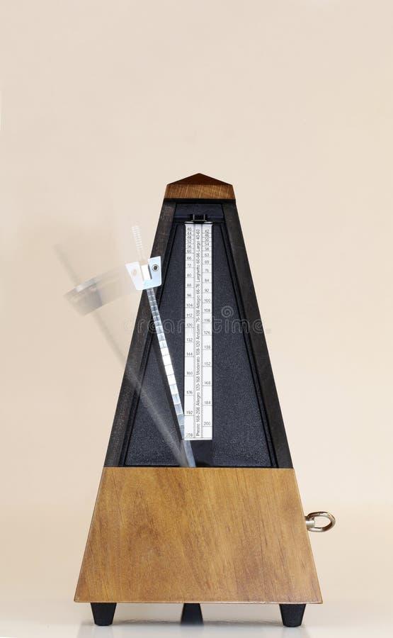 Metrónomo con el fondo móvil borroso de Brown del brazo fotos de archivo libres de regalías