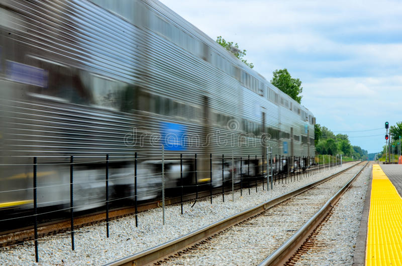 A Metra passenger commuter train blurs past royalty free stock image