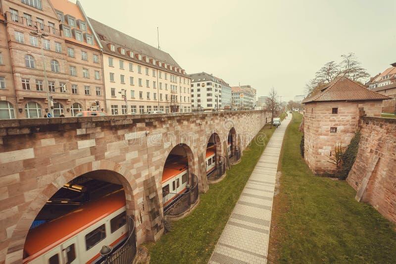Metra taborowy jeżdżenie pod mostem w dziejowym Bawarskim mieście z fort ścianami zdjęcie royalty free