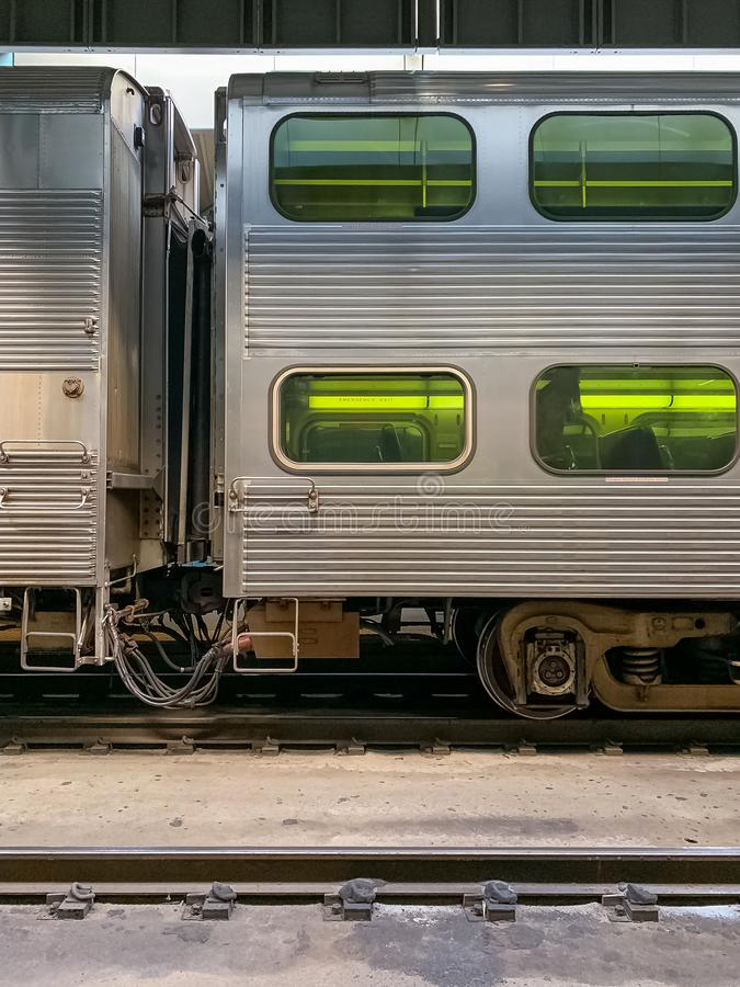 Metra train on railroad tracks in terminal of train station in Chicago, with view through window of passenger taking a seat stock images