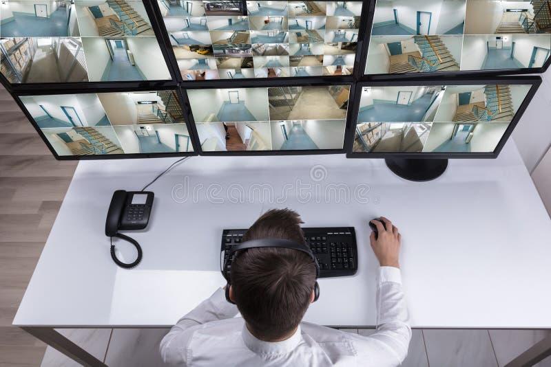 Metragem de Monitoring Multiple Camera do agente de segurança no computador fotografia de stock royalty free