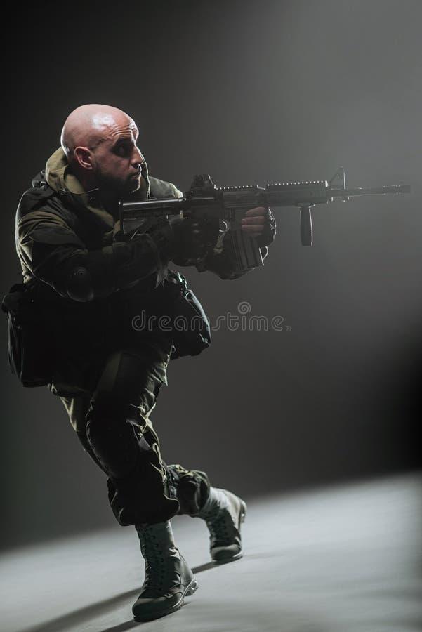 Metralhadora da posse do homem do soldado em um fundo escuro fotografia de stock