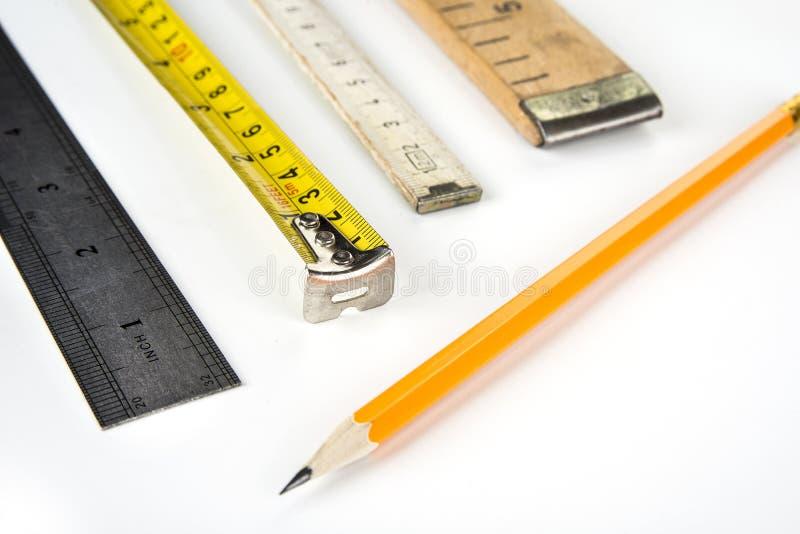 Metri vari su un fondo bianco con la matita immagini stock libere da diritti