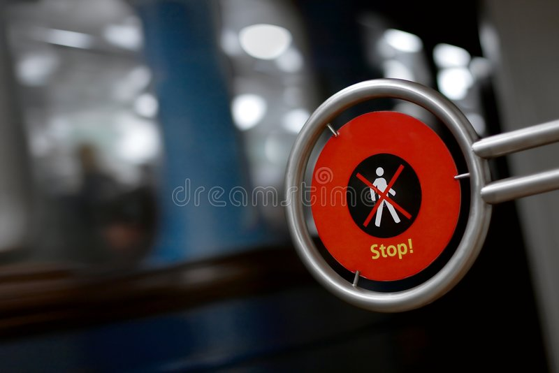 Metro. Warning sign far pedestrians with metro vehicle passing by with motion blur stock image