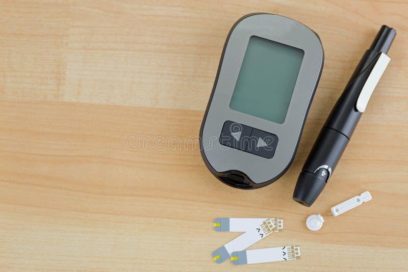 Metro de la glucosa en sangre, tira de prueba, dispositivo lancing de la pluma en vagos de madera imágenes de archivo libres de regalías