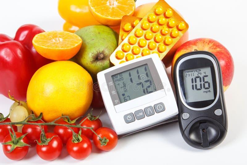 Metro de la glucosa, monitor de la presión arterial, frutas con las verduras y píldoras médicas imagen de archivo libre de regalías