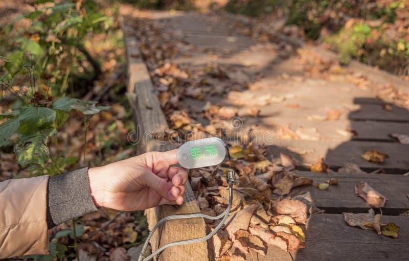 Metro de oxígeno de la sangre en el finger de la mujer Día asoleado del otoño fotos de archivo