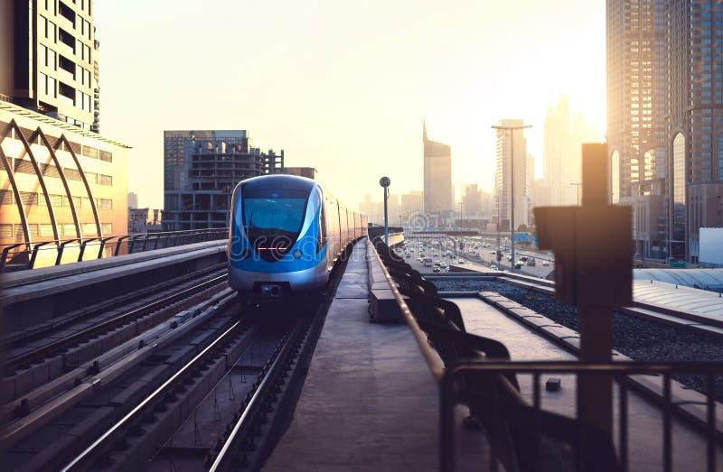 Metro en la puesta del sol en ciudad moderna Metro de Dubai Horizonte céntrico con ocaso Tráfico de los edificios y de coche del  foto de archivo