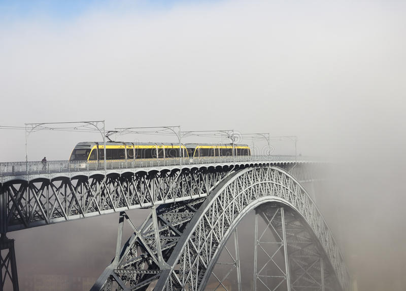 Metro Train on the Bridge Built by Eiffel in Porto. Foggy morning royalty free stock photography