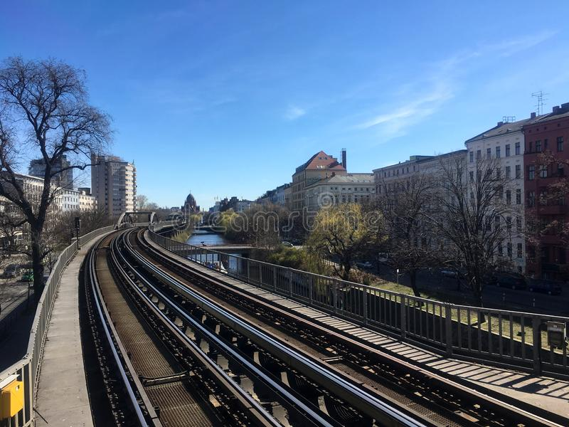 Metro Train U-Bahn Tracks going through Berlin next to Landwehrkanal and Houses in sunny spring weather with blue sky. Berlin. Public Transportation is one of royalty free stock photo