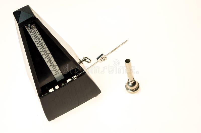 Metronom och munstycke av en trumpet som isoleras på en tom vit fotografering för bildbyråer