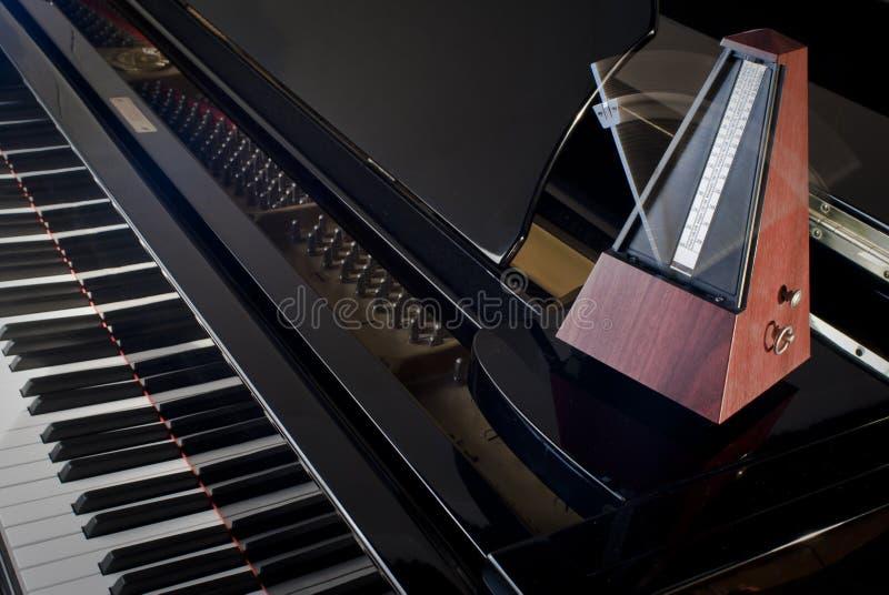 Metronome on a grand piano royalty free stock photos