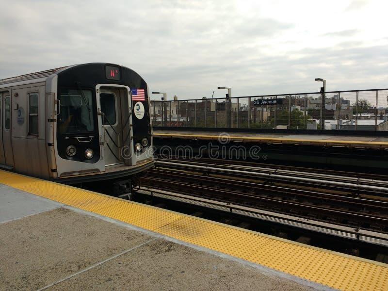 Metropolitana che tira nella stazione, treno di N, trentaseiesimo viale, Astoria, Queens, NYC, NY, U.S.A. fotografia stock libera da diritti