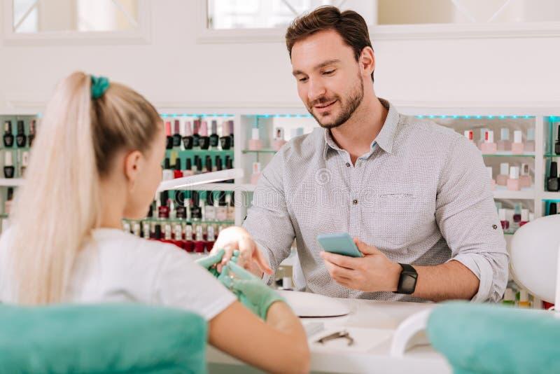 Metrosessuale che si preoccupa per il suo sembrare che ottiene manicure in salone fotografie stock libere da diritti