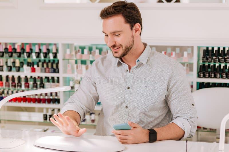 Metrosexualmens die zijn spijkers na het krijgen van manicure bekijken stock afbeelding