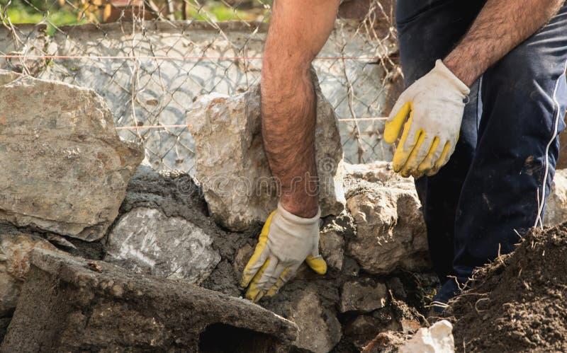 Metselaar die een steenmuur, authentieke werkende persoon bouwen royalty-vrije stock fotografie