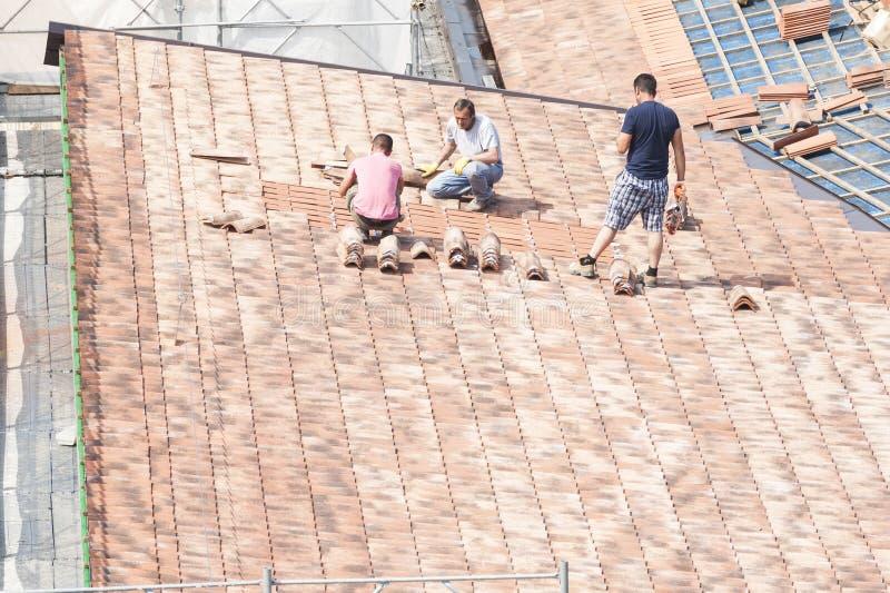Metselaars om aan het dak te werken voor het leggen van tegels royalty-vrije stock foto's