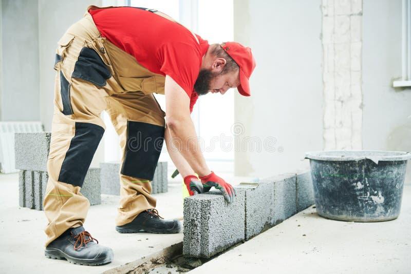 metselaarsbouwer die met ceramsite concrete blokken werken muur stock foto