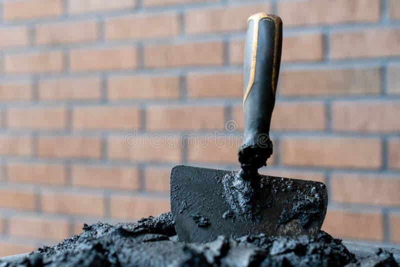 Metselaarstroffel in vers mortier met bakstenen muur n de achtergrond royalty-vrije stock afbeeldingen