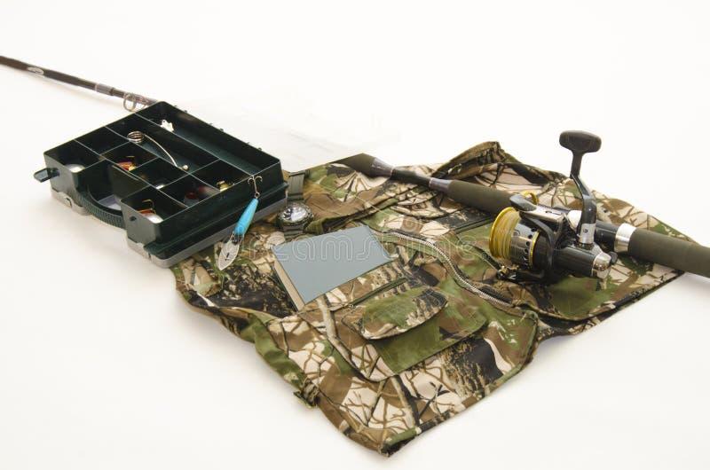 Metspö med rull- och fisketillbehör på kamouflagejacke arkivfoton