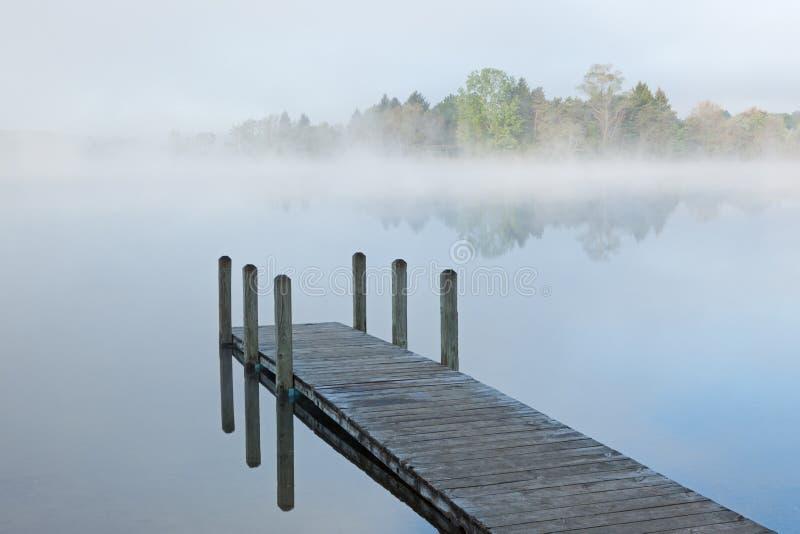 Metta in bacino sul lago nebbioso immagini stock libere da diritti