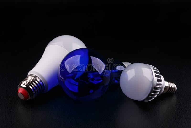 Metta con differenti tipi di lampadine su fondo nero immagini stock