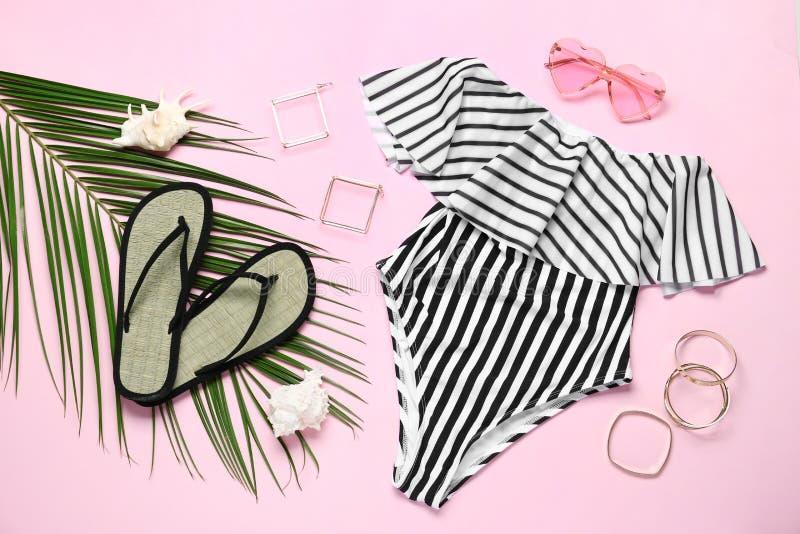 Metta degli accessori e del costume da bagno delle donne alla moda su fondo rosa immagini stock libere da diritti