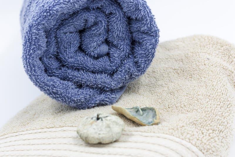 Metta degli asciugamani di bagno con i fiori secchi e le pietre blu del mare immagini stock