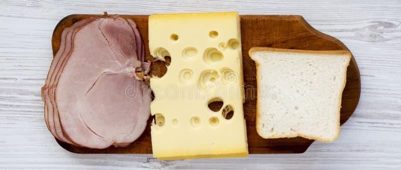 Metta degli ingredienti per produrre il panino: pane, formaggio e bacon del pane tostato su superficie di legno bianca closeup fotografie stock libere da diritti