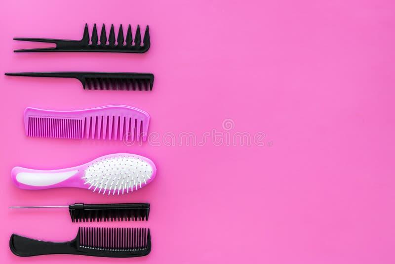 Metta degli strumenti professionali del parrucchiere con il modello rosa di vista superiore del fondo dei pettini immagini stock