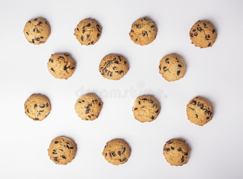 Metta dei biscotti con i pezzi di cioccolato disposti simmetricamente su fondo bianco immagini stock libere da diritti