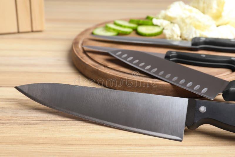Metta dei coltelli e delle verdure crude fresche sulla tavola di legno immagini stock