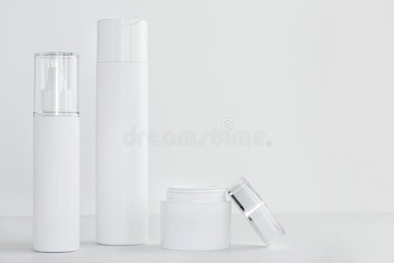 Metta dei contenitori bianchi dei cosmetici su fondo leggero Copi lo spazio fotografia stock