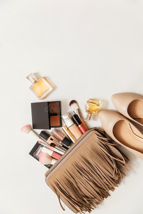 Metta dei cosmetici della donna in una borsa Segreti del ` s delle donne Cosmetici, profumo, spazzole, polvere, evidenziatore, co immagine stock
