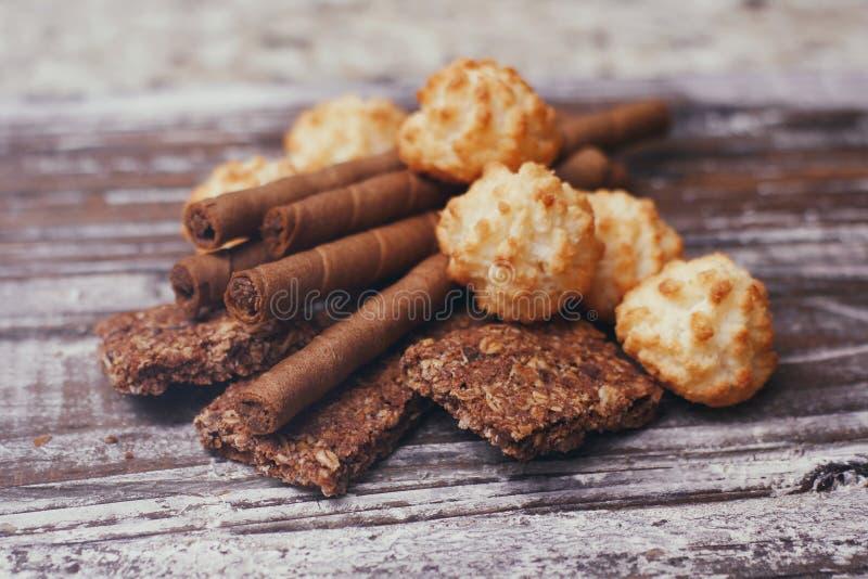 Metta dei dolci differenti della confetteria sulla tavola di legno Cioccolato, cialde, biscotti della noce di cocco, biscotti immagini stock