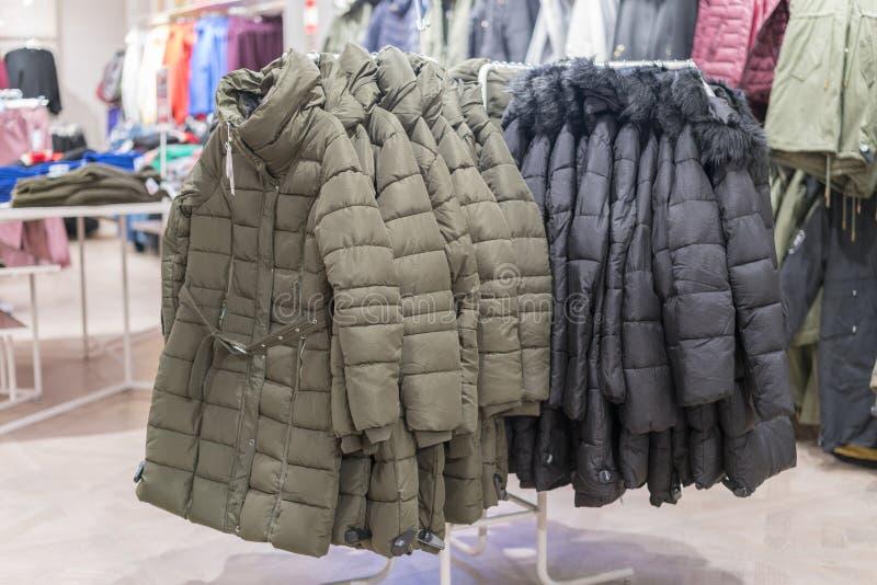 Metta dei vestiti, cappotto sull'interno del negozio dell'abbigliamento dello scaffale su fondo Rivestimenti di inverno in un dep immagini stock libere da diritti