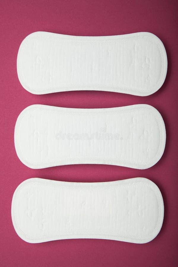 Metta del cuscinetto mestruale quotidiano della donna, l'igiene, periodo del sangue su fondo rosso fotografie stock