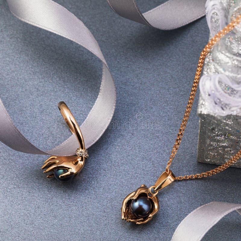 Metta del pendente e dell'anello dei gioielli dell'oro con le perle e gli zirconi neri immagini stock