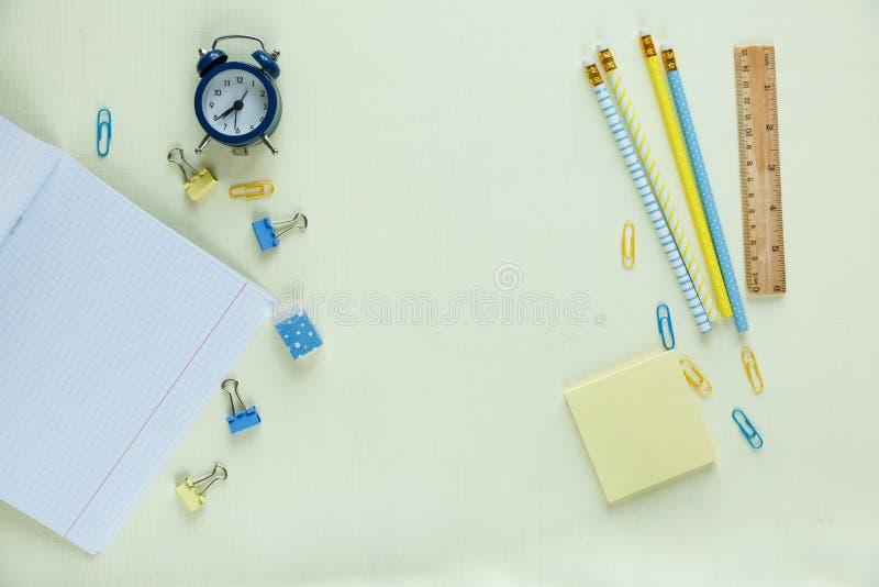 Metta della cancelleria della scuola di nuovo a scuola: matite, orologio, blocco note, righello su fondo giallo istruzione, lezio fotografie stock