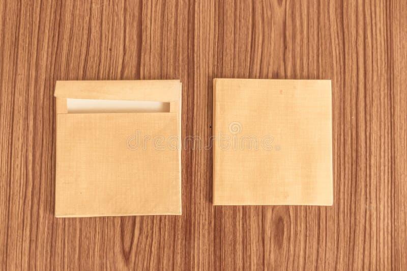Metta della parte anteriore della busta di due Brown ed indietro isolato sul fondo di legno del pavimento di legno duro della tav fotografia stock libera da diritti