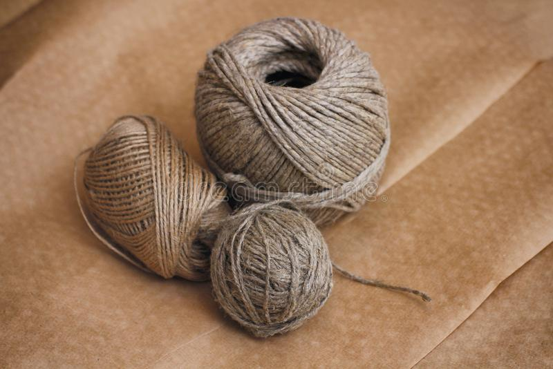 Metta delle palle delle corde sulla carta del mestiere Tela, cotone della canapa Materiali da imballaggio immagini stock